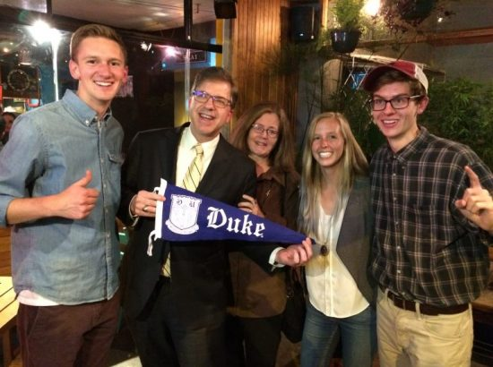 Two male DukeEngage students pose with Duke pennant and three adults