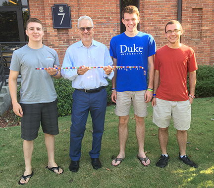 Three young men present faculty member with colorful walking staff