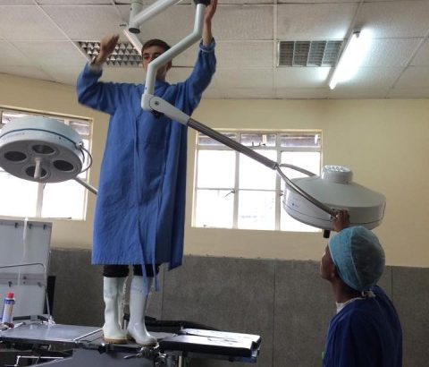 People in a medical workspace adjust a light.