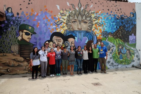 People in front of a large mural