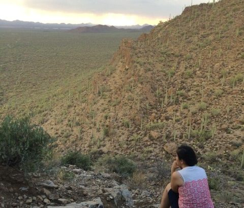 Woman seated on a rock looking at desert land