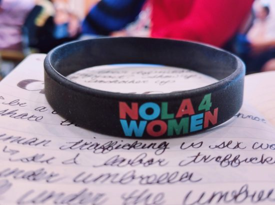"""Wristband reading """"Nola 4 Women"""" on top of notebook paper"""