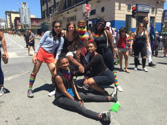 Group of people in street dressed in rainbow clothing