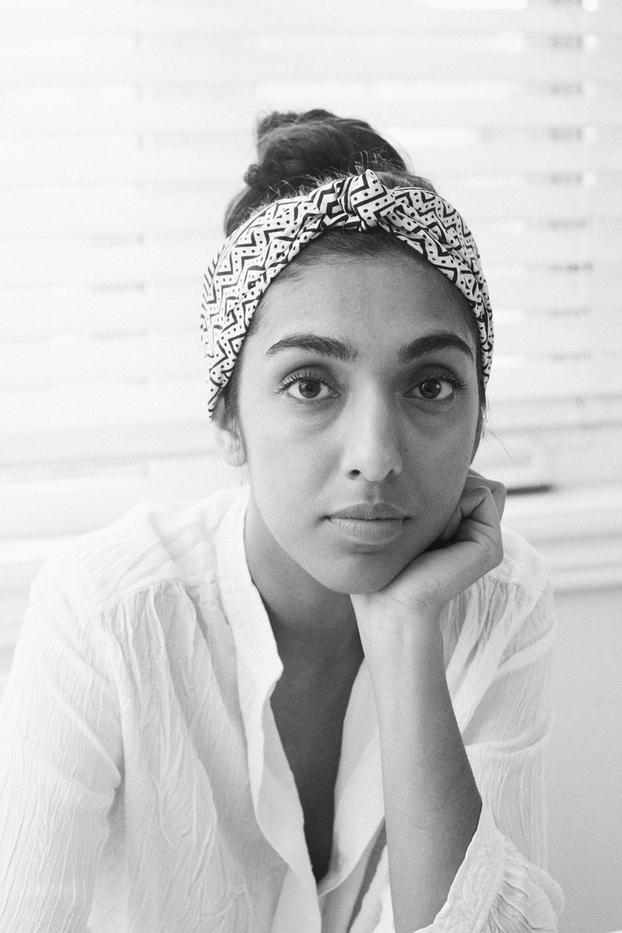 A black and white headshot of the poet Rupi Kaur