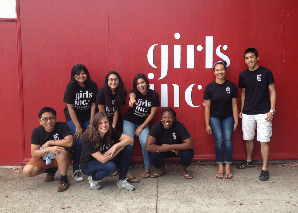 DukeEngage students posing in front of a sign for Girls Inc