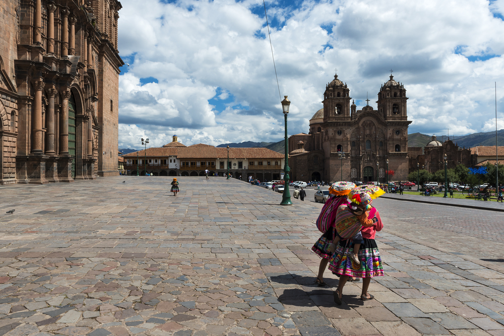 Courtyard in Cuzco, under a blue sky with white clouds