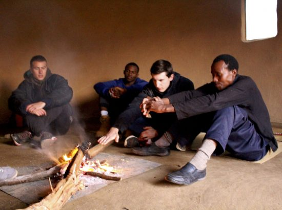 Four men gathered around fire