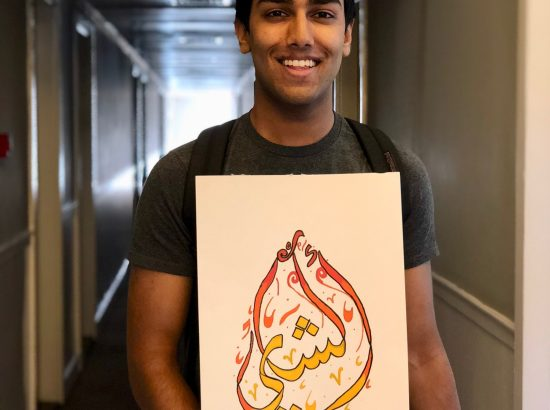 man smiling in a hallway holding a painting of words with yellow red and orange colors
