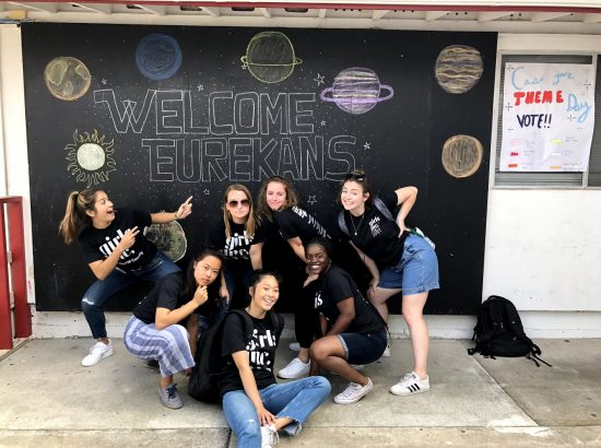 """Group of people posed in fronts of Chalkboard wall reading """"Welcome Eureakans"""" with drawings of planets"""