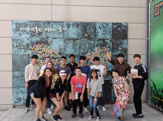 Group of young people in front of artwork on wall
