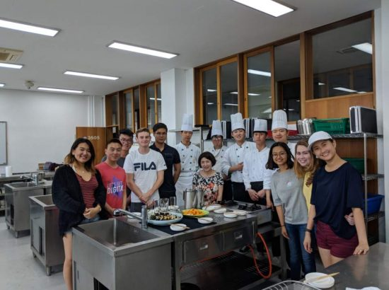 Group of people in kitchen with others wearing chef outfits