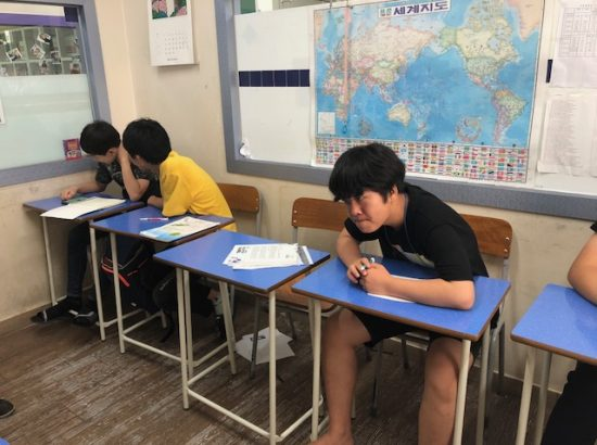Young people working at desks in a classroom