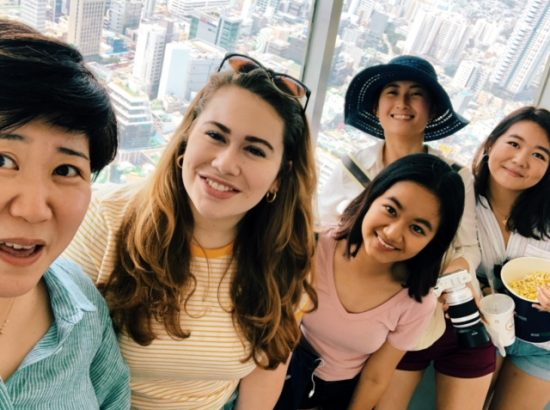 Selfie photo of five people standing in front of high-rise window with city buildings outside