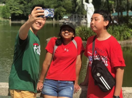 Three people taking selfie in front of body of water with statue in distance