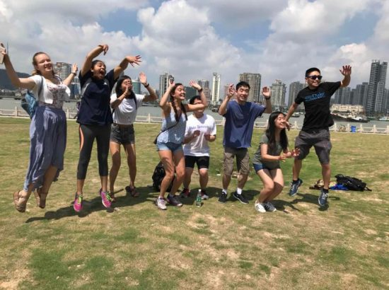 Eight students outdoors jumping in front of city skyline