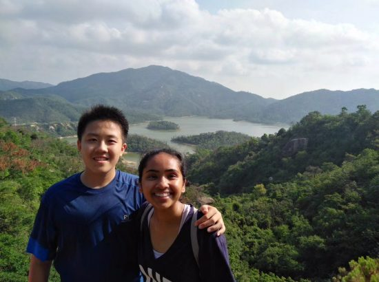 Two people above view of water and grassy mountains