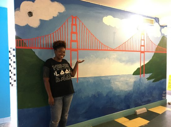 woman stands by mural of San Fransisco Bridge