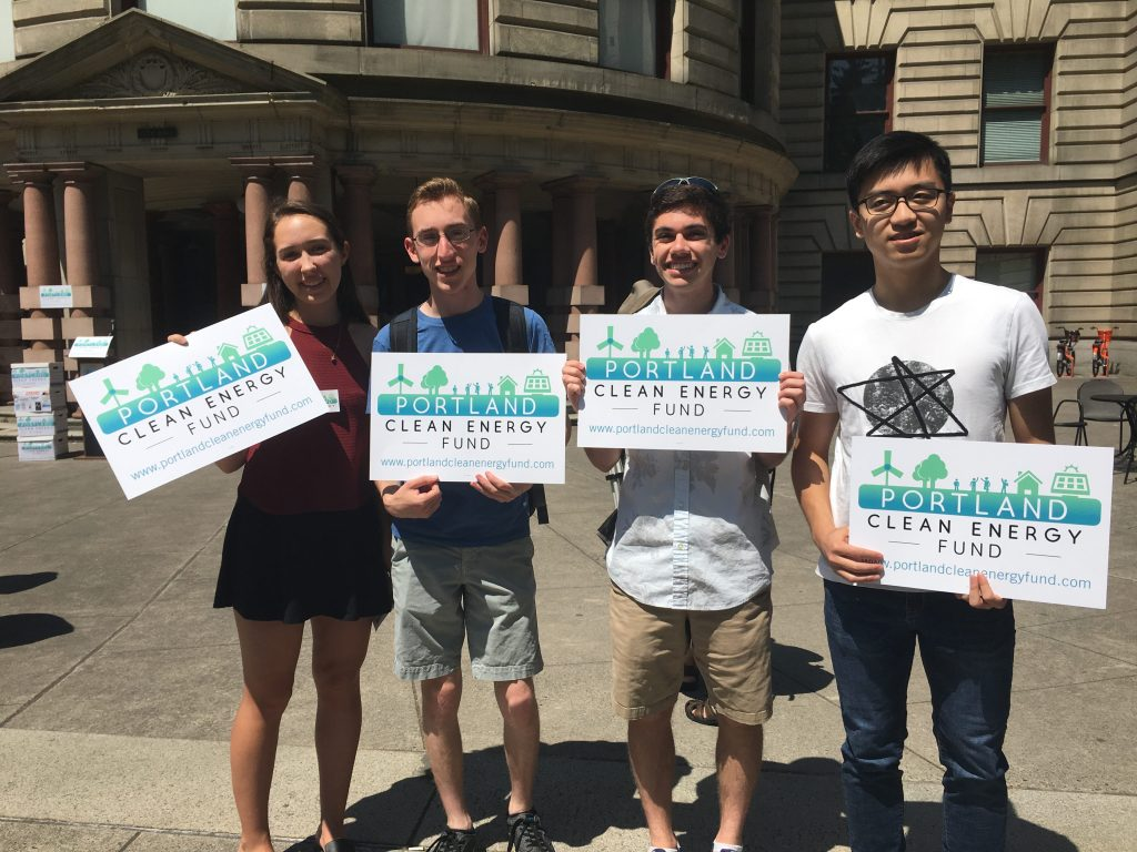 "Four people holding signs reading ""Portland Clean Energy Fund"""