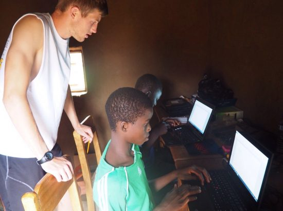 DukeEngage student working with two children on computers