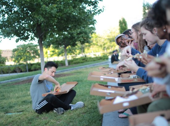 Group of people seated outdoors eating from pizza boxes