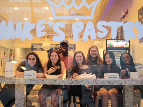 "Group of people in bakery window under the words ""Mike's Pastry"""