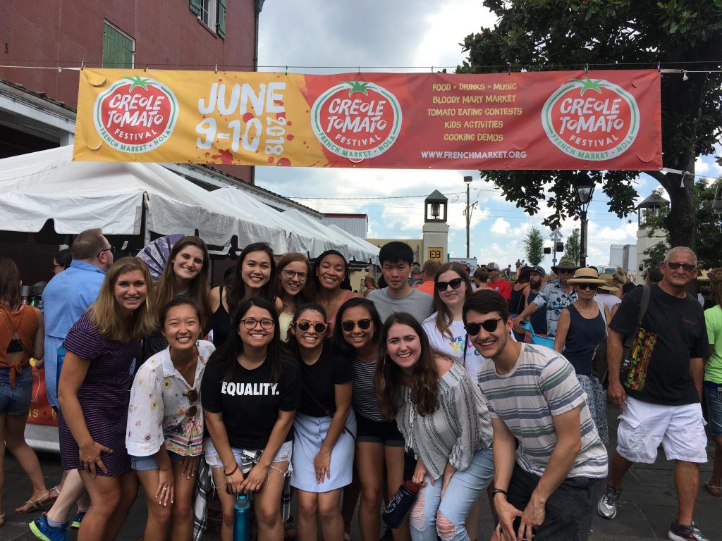 Group of students at street festival gathered under festival banner