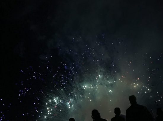 Silhouettes of people in front of fireworks display