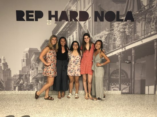 """Five people standing in front of large photograph of New Orleans under words reading """"Rep Hard Nola"""""""