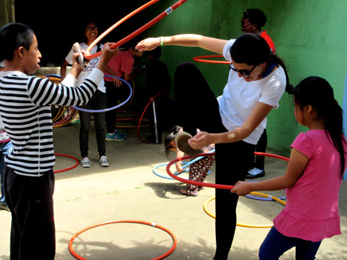 Women and children playing with hula-hoops