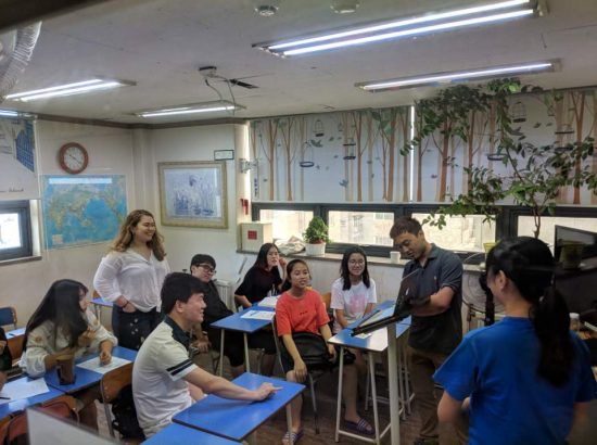 Group of people in a classroom. One person showing a laptop to seated students.