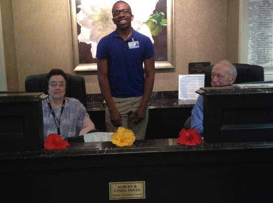 Three people behind a desk smiling