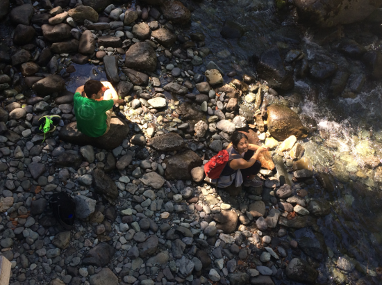 Two students sitting by a stream