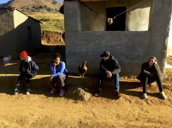four students perched on stoop in South Africa