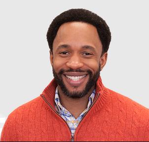 Man in orange sweater smiling