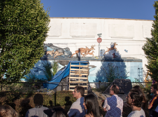 People gathered in front of mural