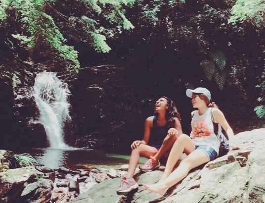 Two women sit on a rock in front of a waterfall