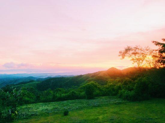 Sunset behind grassy hills