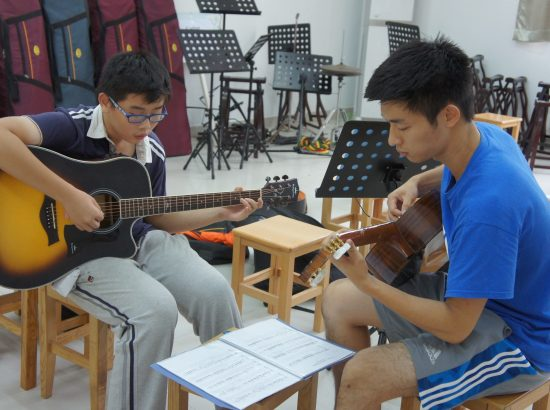 young man and young boy playing guitar facing one another in a classroom