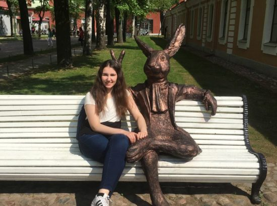 Person seated on bench next to statue of rabbit