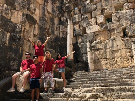 group wearing red shirts enclosed by rocks and on tope of stairs, point to the rocks and columns around them