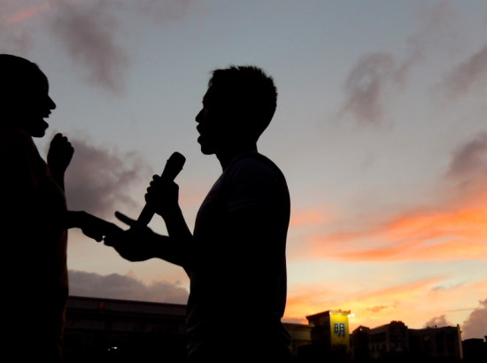 Silhouettes of people speaking into microphone