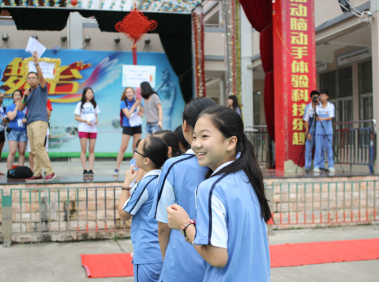 Students watch others on an outdoor stage