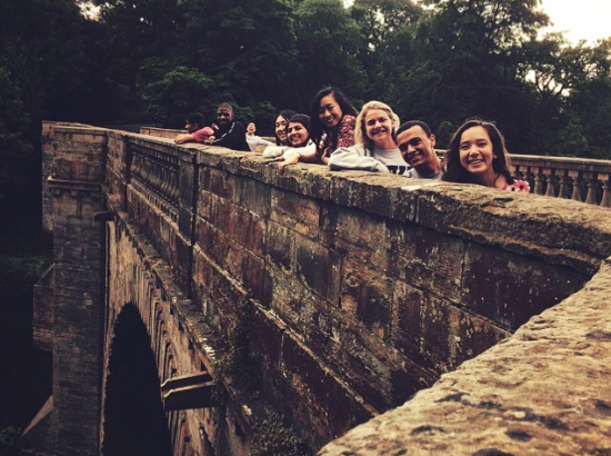 Students lean against a ledge atop a stone bridge