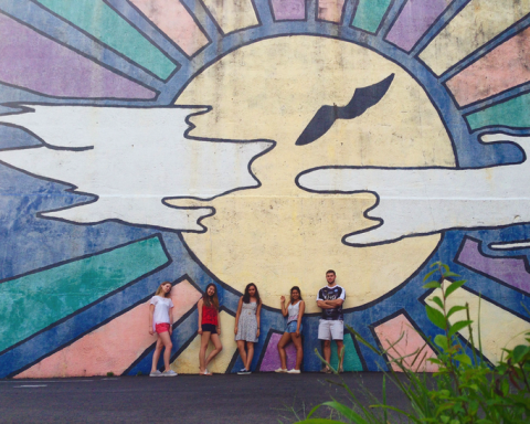 Students posed in front of a abstract mural of the sun
