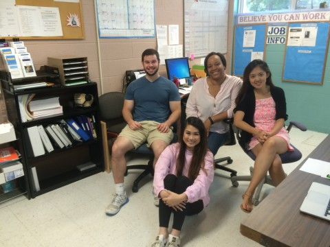 Students and adult seated in an office