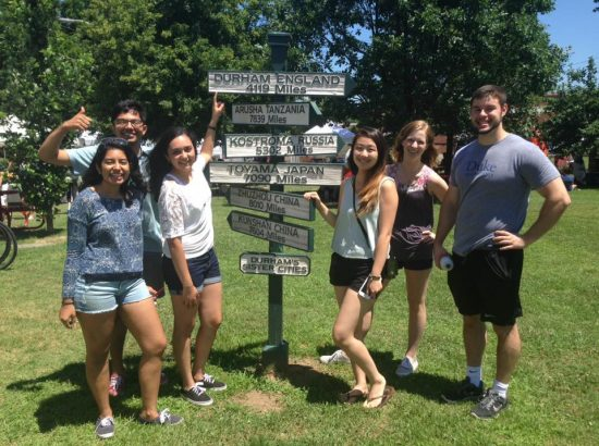 A group of college students standing around a road sign