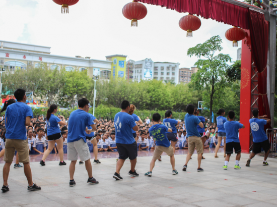 Students dancing on an outdoor stage for large audience