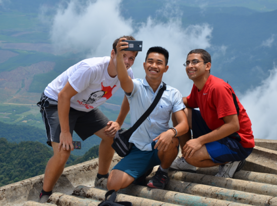 Students take picture of themselves with view of mountains in the background