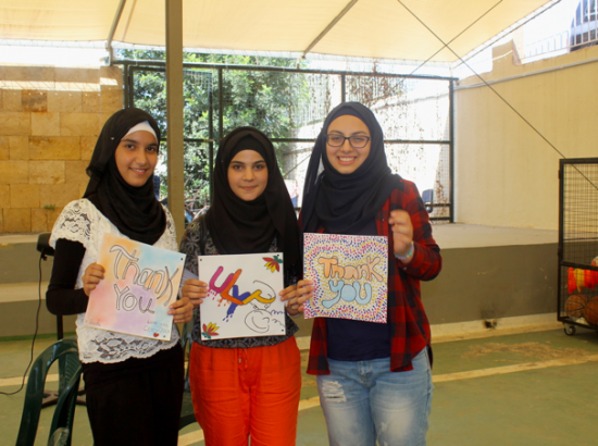 Three young women holding works of art with messages of gratitude