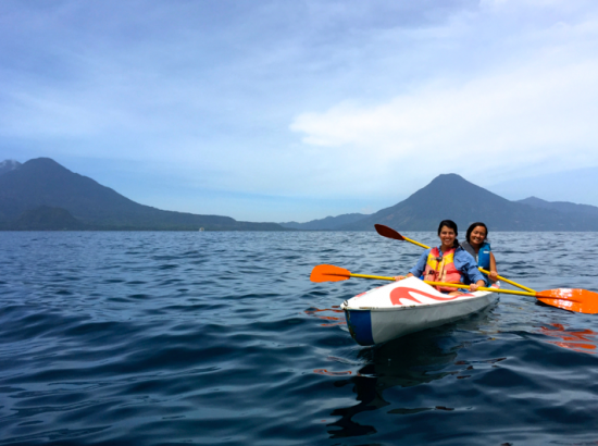 Students riding in kayak with mountains in background